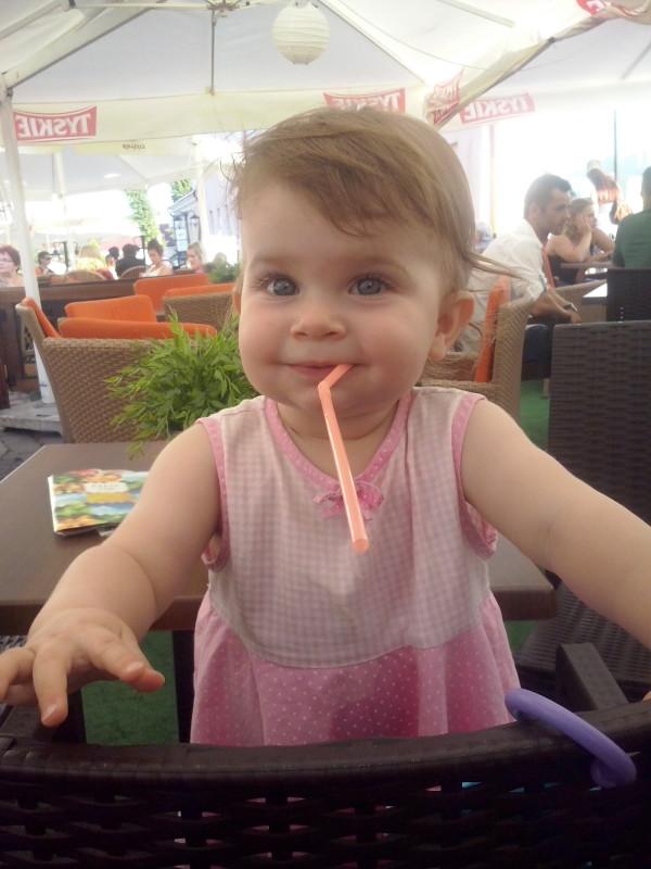 Mała dziewczynka ze słomką w ustach