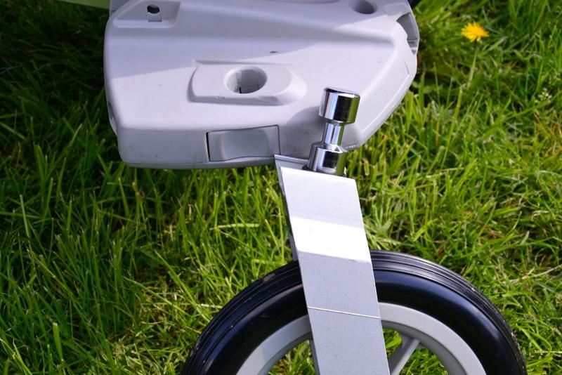 Jak włożyć kółko przy składaniu wózka spacerowego? Jeden otwór, jeden przycisk, jeden klik.